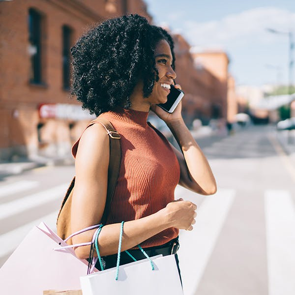 Woman walking across the street on the phone with shopping bags