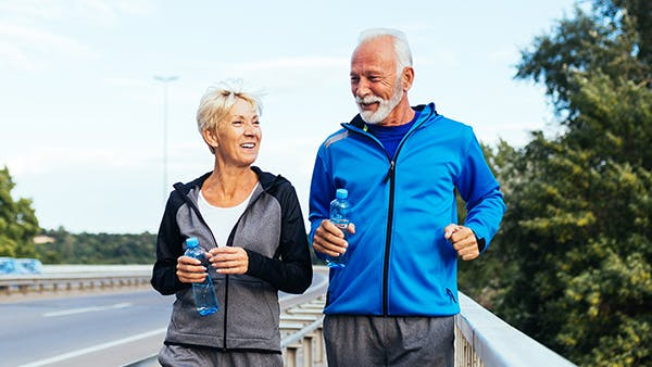 Older couple walking down a road to exercise