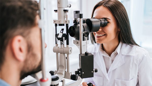 Optometrist checking someone's eyes with a machine