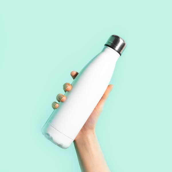 Hand holding water bottle against colorful background