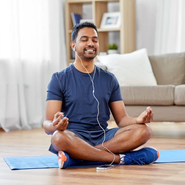 Happy man meditating in his home