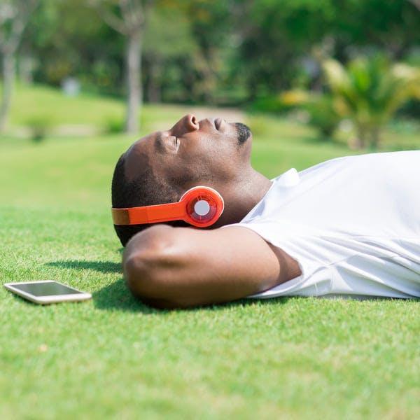 Man resting in park wearing headphones