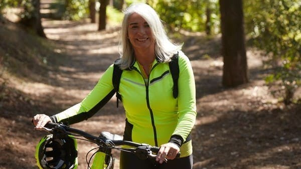 middle aged woman in neon workout gear with bike on a trail