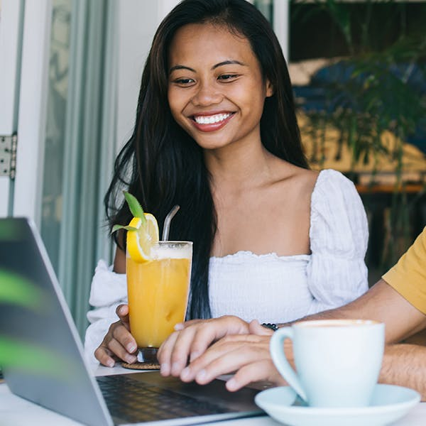 Smiling woman holding a drink looking at a laptop