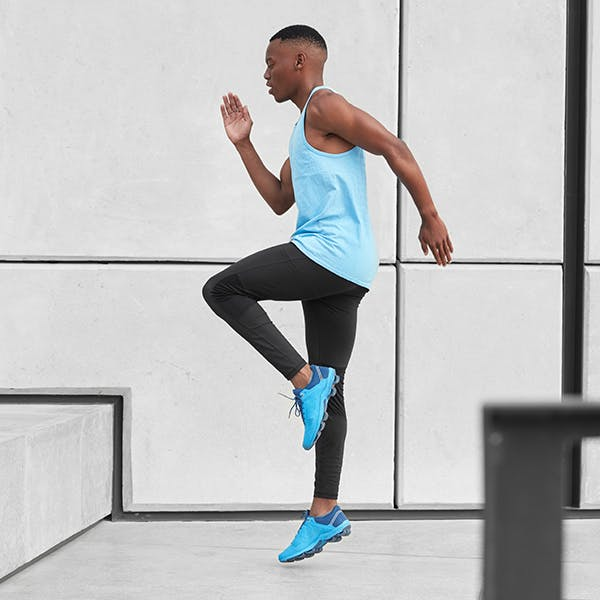 Young man doing high knee exercises in workout clothes