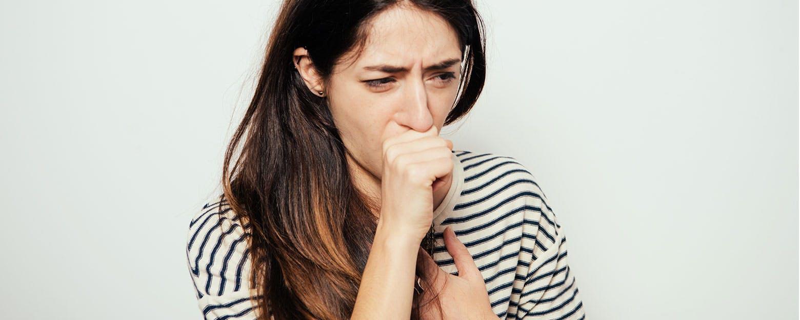Femme qui tousse à cause d'une congestion de la poitrine