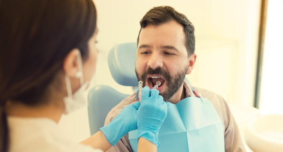 A man having a retainer fitted by a dentist