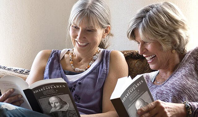 two women reading books and smiling with dentures