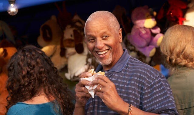 A man enjoying a sandwich looking confident with his dentures