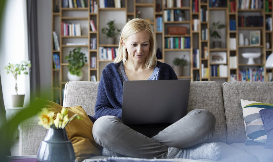 Woman sitting cross-legged on her couch while reading  something on her computer