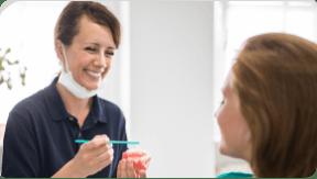 A dentist holding a set of full dentures