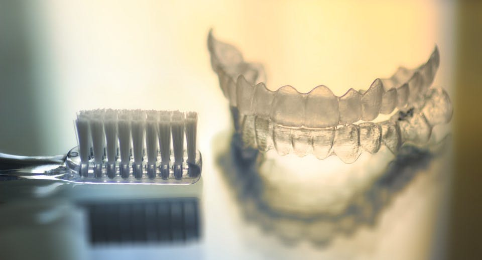 A soft bristled toothbrush and a set of dental retainers