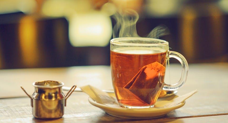 A steaming hot glass mug of tea on a table