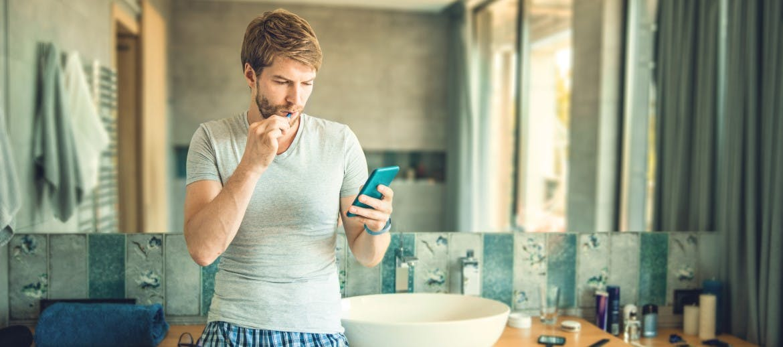 A man brushing his teeth and looking at his phone