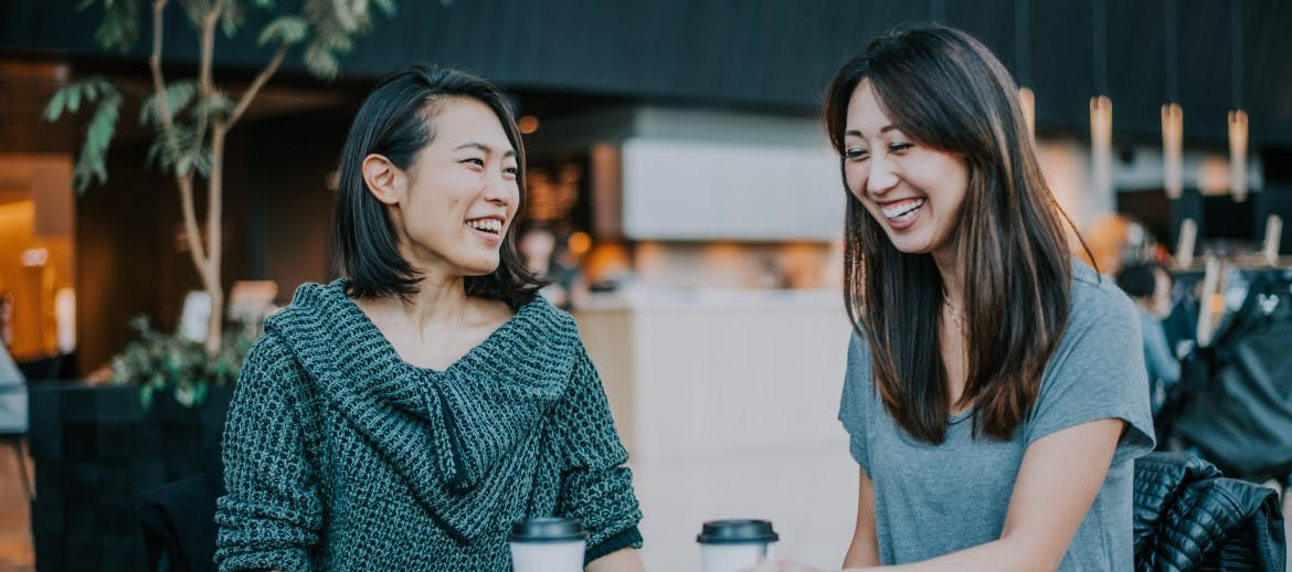 two women laughing over a coffee
