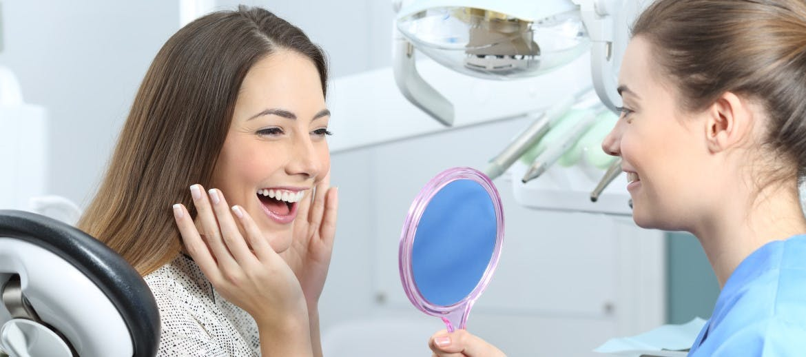A women smiling into a mirror at the dentist