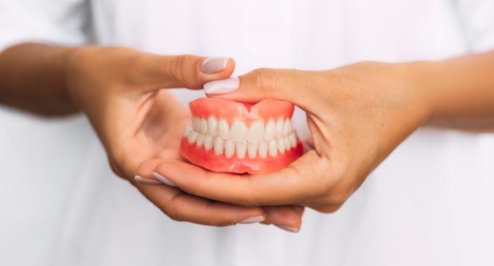 a set of full dentures being held in hands