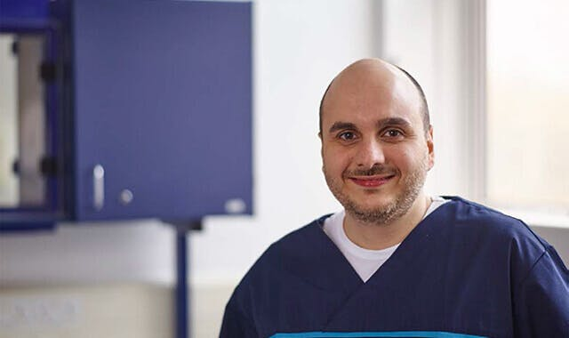 Dentist dressed in scrubs smiles directly at camera