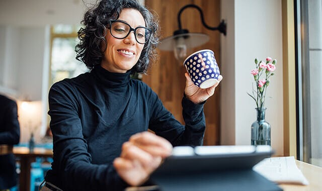Woman with glasses sitting at a table in her dining  room while looking at her tablet