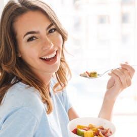 Lächelnde Frau hält Karotte in der Hand