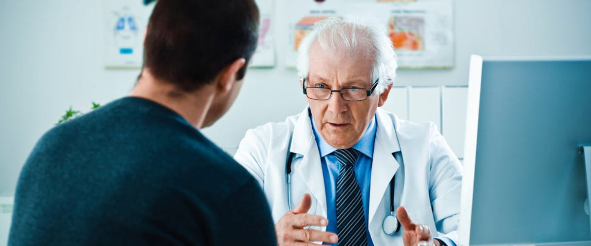 man talks to his doctor about sleep and headaches