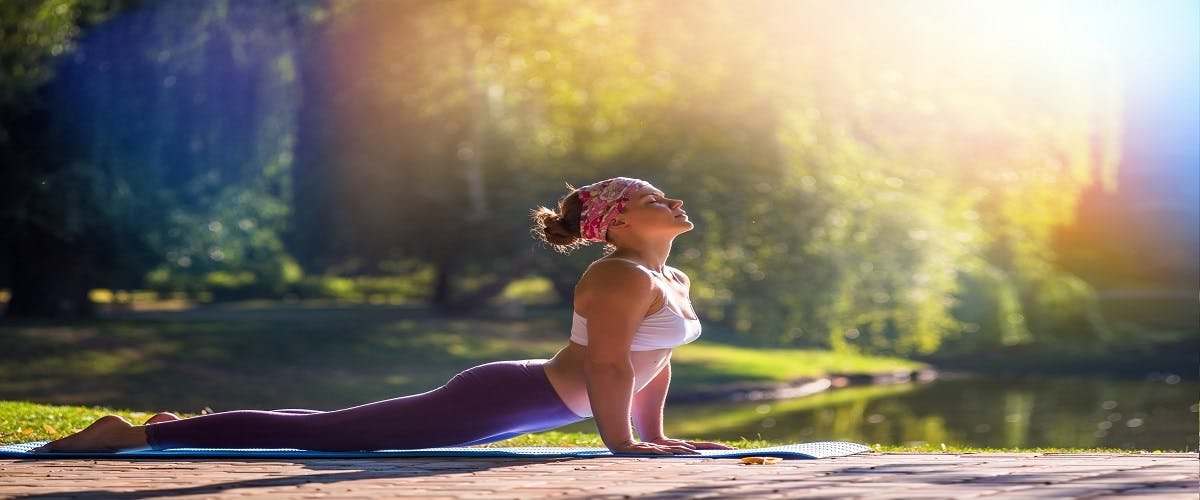 Relaxed young woman doing morning yoga in a park next to trees and a lake