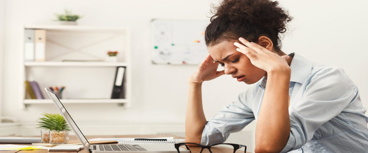 A woman looks away from her computer with a headache
