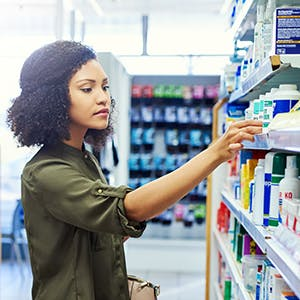 woman in a green shirt shopping at a pharmacy
