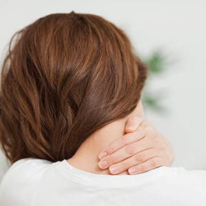 woman with brown hair experiencing neck and upper shoulder pain