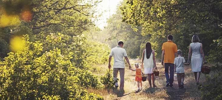 Οικογένεια με φίλους περπατούν στο δάσος