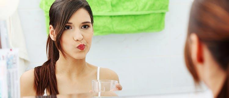 Frau beim Mundspülen