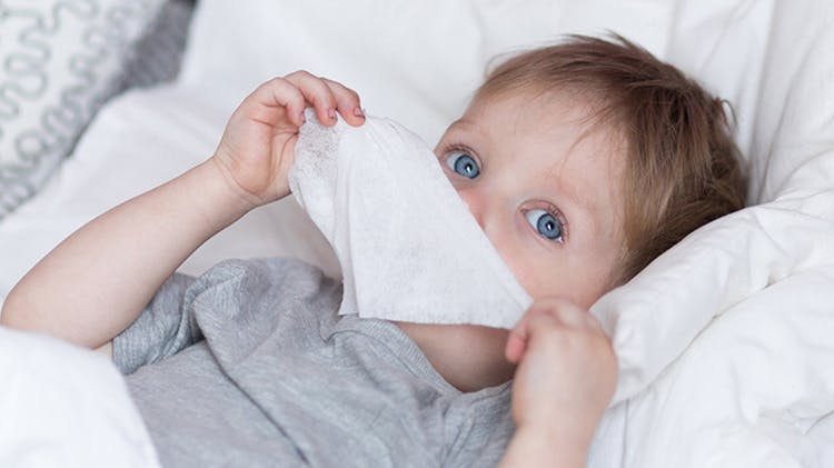 Child suffering a cold in bed