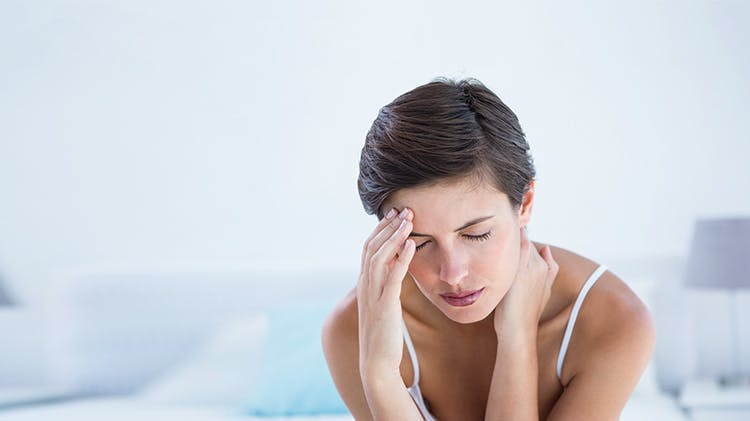 Woman touching her forehead in pain