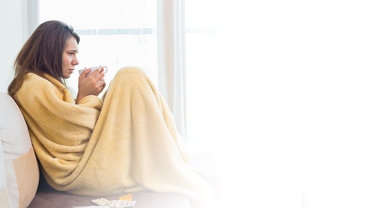 Woman unwell under blanket