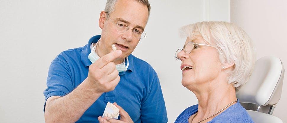 Man showing woman a denture