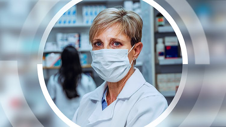 A pharmacist wears a face mask to help protect herself against COVID-19.