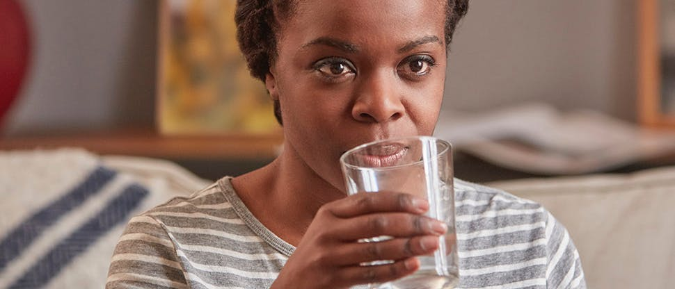 Woman drinking water to treat Dry Mouth