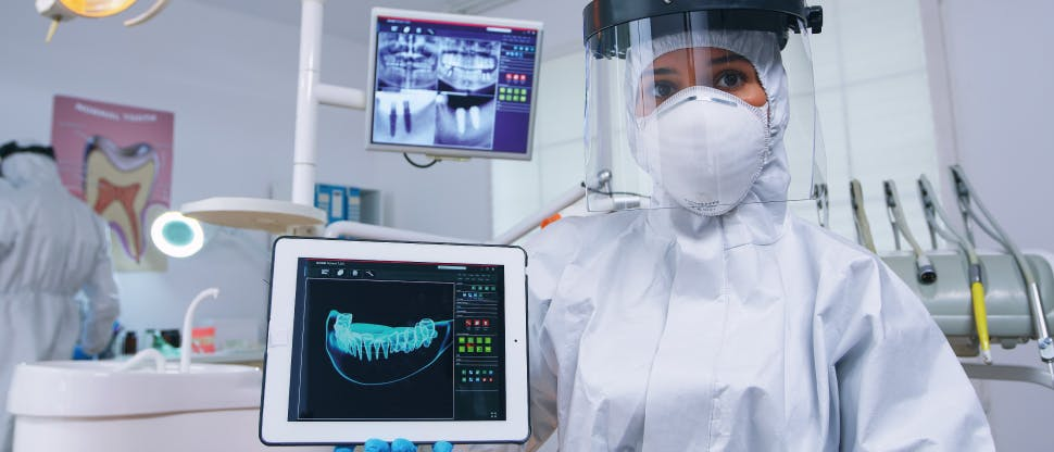 Denrist showing a patient the x-ray of your teeth and pointing out dentin