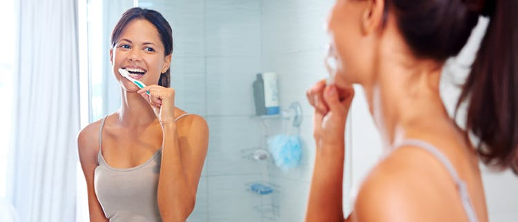 Woman brushing teeth to maintain healthy gums