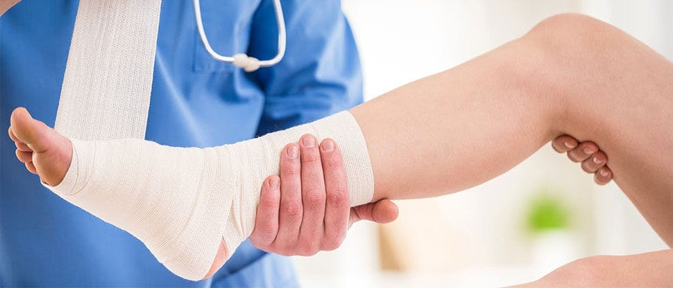 Close-up of male doctor bandaging foot of female patient at doctor's office