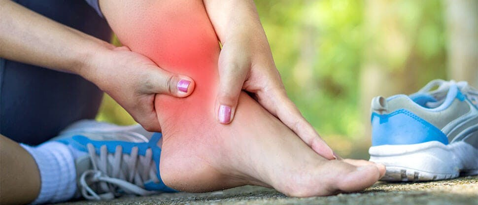 Woman massaging painful ankle injury