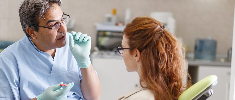 Male orthodontist with glasses conversing with female patient as she sits in the appointment chair