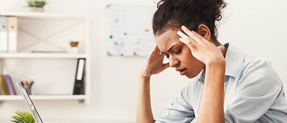 Woman at a desk with a headache