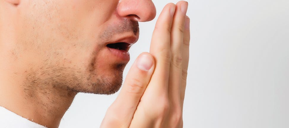 Young man testing his breath with his hand