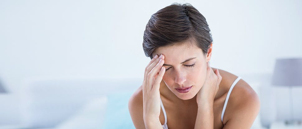 Lady holding her forehead in pain