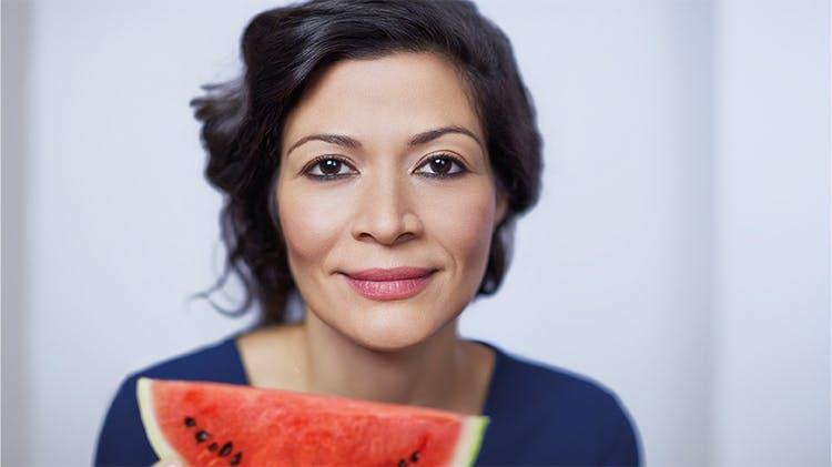 Une femme tenant une tranche de melon