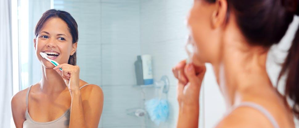 Une femme se brosse les dents et sourit