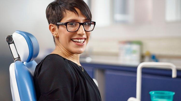 Professionista dentale con gli occhiali che sorride alla fotocamera