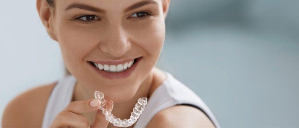 Femme tenant l'appareil dentaire et souriant