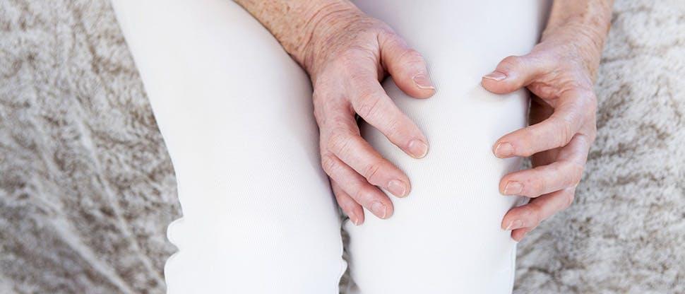 Kobieta trzymająca się za kolano